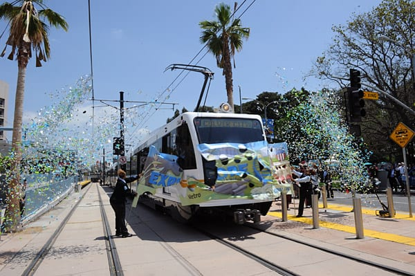 Operator Carolyn Kelly is at the controls of the inaugural train at the opening of the Expo Line. Operator Sheila Celestain, at left, is holding the banner. Barely visible, holding banner at right, is the third original Expo Line operator, Narvolean Jackson.