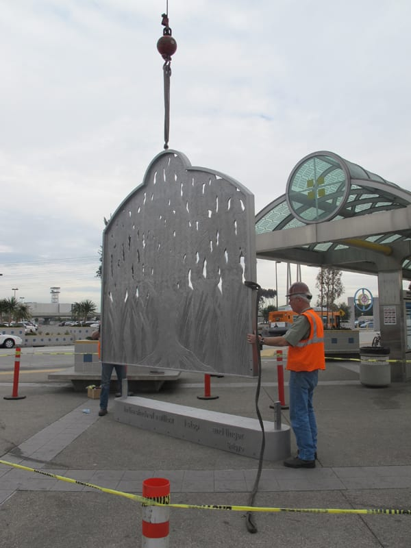 Workers set the sculpture into its base