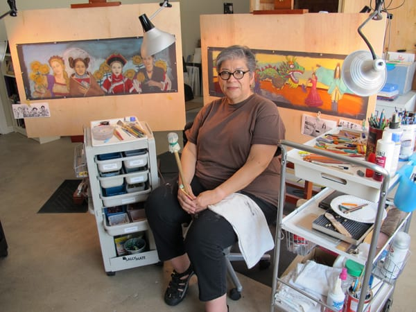 Artist Judithe Hernandez in her studio, with two of her original artworks for the Expo Line in the background.