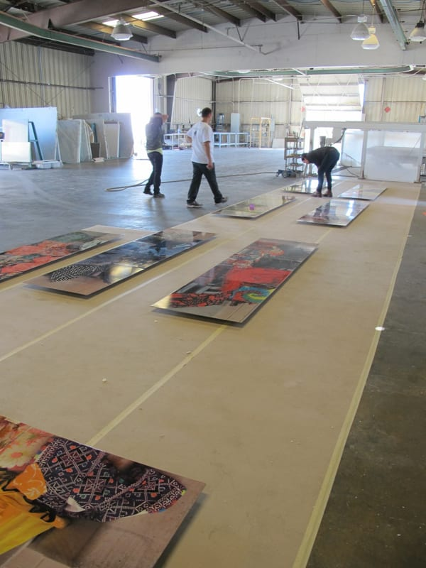 Argote inspecting her artwork panels with Metro Art staff after they were delivered by artwork fabricator Winsor Fireform to ensure that her original artworks are accurately depicted, and that the photographic quality is is consistent among all twelve.