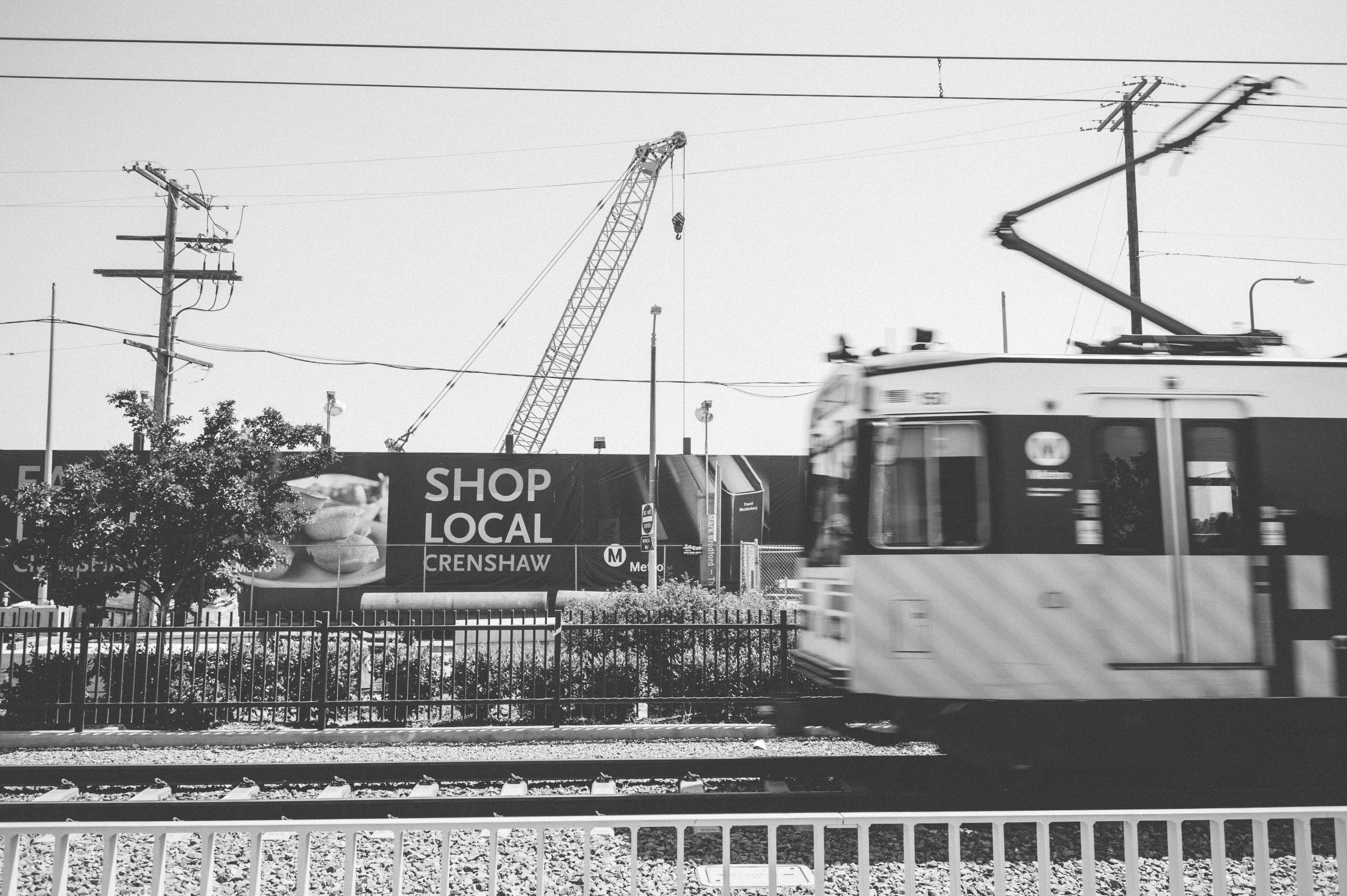 An Expo Line train passes the construction site for the Crenshaw/Expo Station for the Crenshaw/LAX Line.